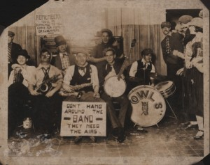 New Orleans Owls (jazz band) at Chess, Checkers and Whist Club, formerly Cosmopolitan Hotel. Musicians left to right: Mackie, R.; Rau, E.; Mackie, D.; Smith, M.; White, B.; Golpi, R.; Crumb, E. The band and spectators at right are costumed; possibly for costume party or Carnival. This photo and information is from Wikipedia (public domain).
